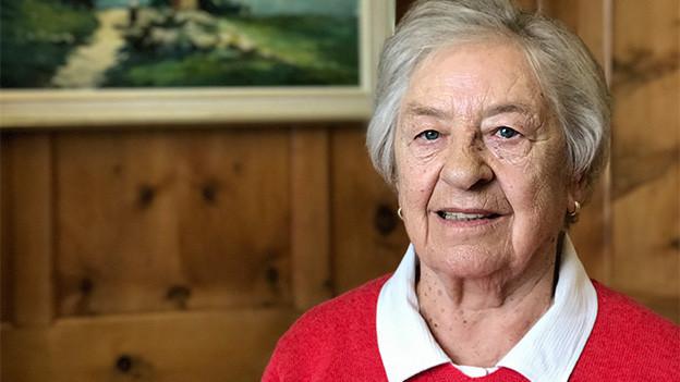 Eine ältere Frau mit einem roten Pullover über einer Bluse.