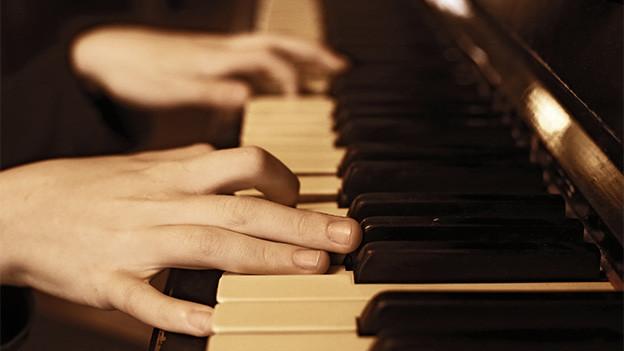 Hände eine jungen Menschen auf Klaviertasten.