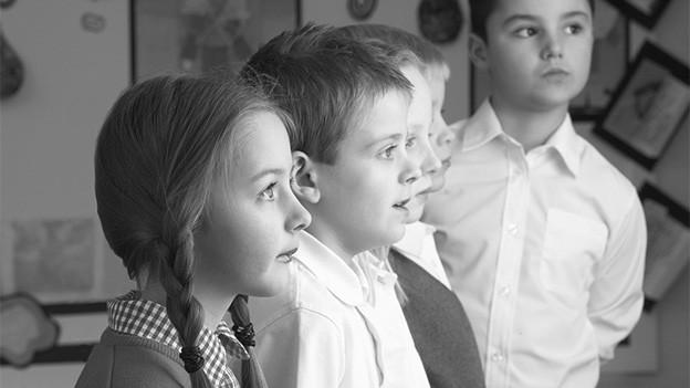 Ein Mädchen und drei Buben einer Schulklasse