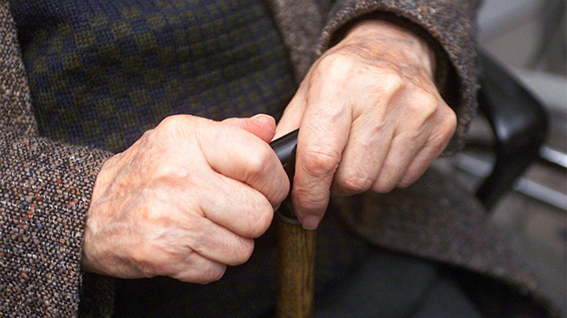 Alte Hände auf einem Gehstock.