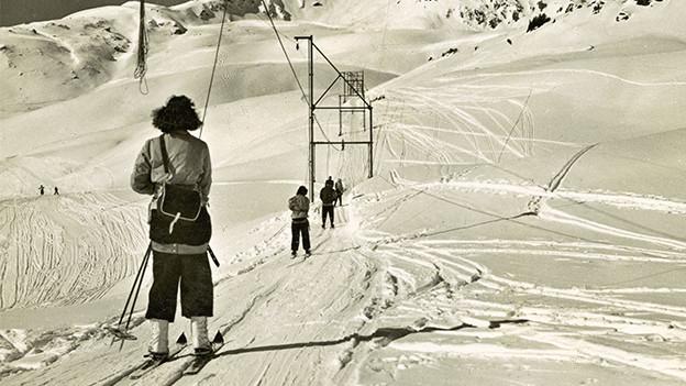 Alte Fotografie mit Menschen auf einem Skilift.