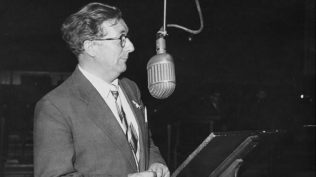 Schwarz-Weiss-Fotografie von einem Mann vor einem Mikrofon.