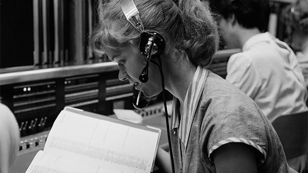 Schwarz-Weiss-Fotografie von einer Frau mit Kopfhörern in einer Telefonzentrale.