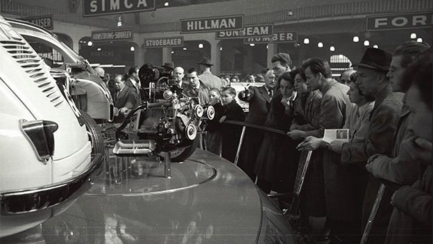 Menschen stehen an einem Stand vor einem Automobil.