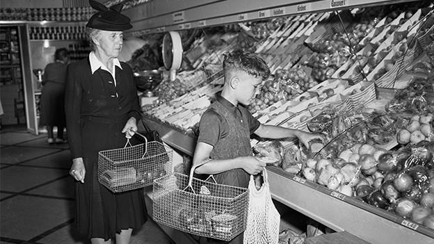 Eine ältere Frau und ein Bub in der Obst- und Gemüseabteilung eines Lebensmittelgeschäfts.