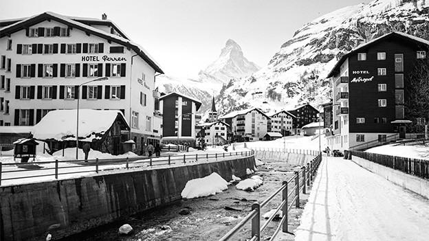 Schwarz-Weiss-Fotografie von einem Dorf in den winterlichen Bergen.