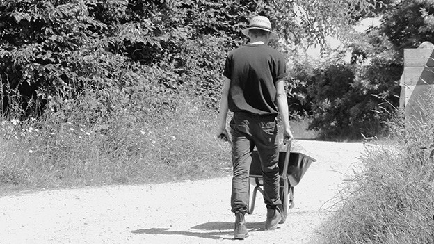 Ein Mann mit einer Schubkarre auf einer verlassenen Strasse.