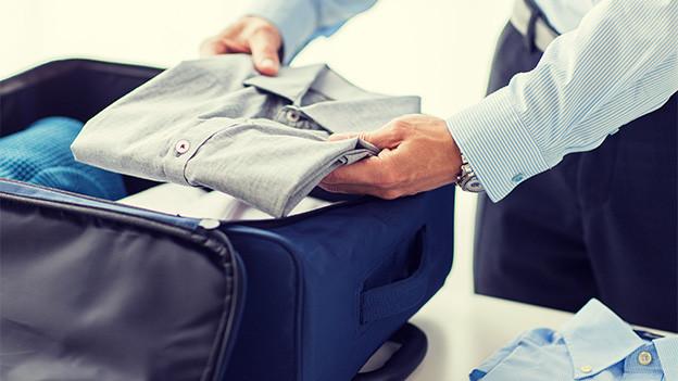 In einen Koffer werden Hemden gepackt.