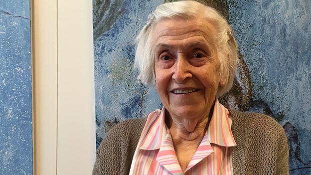Eine ältere Frau vor einem Gemälde in Blautönen.