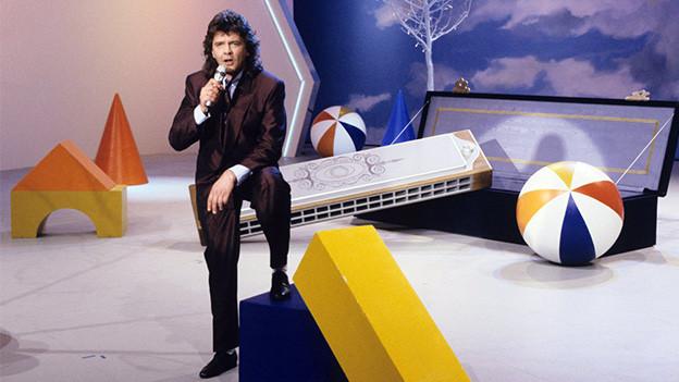 Ein dunkelhaariger Sänger vor einer überdimensionalen Mundharmonika in einem Fernsehstudio.