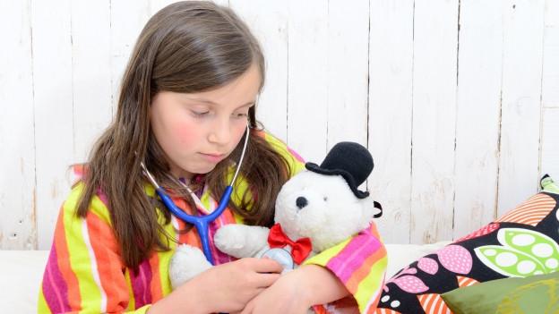 Mädchen hört mit dem Stetoskop ihren Teddybär ab.