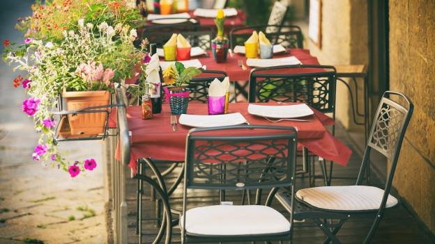 Eine Terrasse mit gedeckten Tischen.