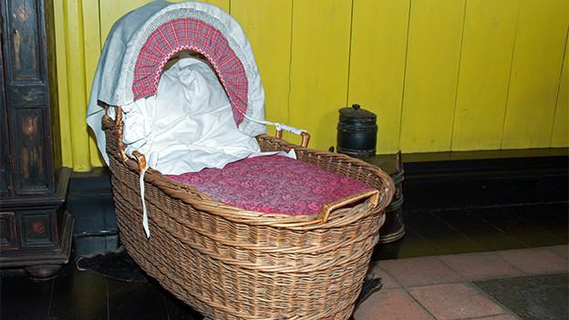 Eine alte Wiege in einem Wohnzimmer mit Kachelofen.
