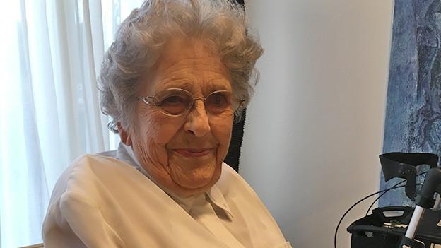 Eine ältere Frau mit Brille sitzt vor einem Fenster.