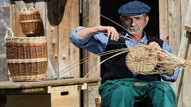 Ein älterer Mann sitzt vor einem alten Haus und flicht Körbe.