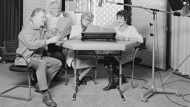 Zwei Männer und zwei Frauen in einem Aufnahme-Studio.