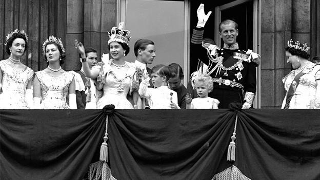 Schwarz-Weiss-Fotografie von Queen Elizabeth II winkend auf einem Balkon.