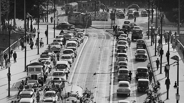 Historische Aufnahmen mit Autos, Tram, Radfahrenden und Passanten auf einer Brücke.