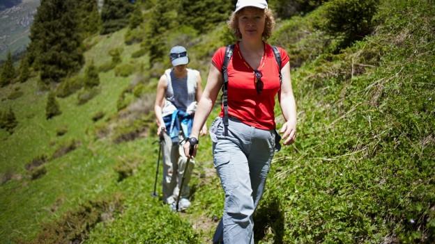 Zwei Frauen wandern auf einem schmalen Weg in den Bergen.