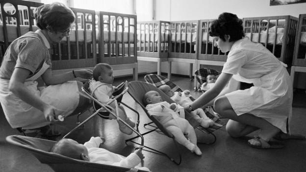 Kleinkinder werden gepflegt und gefüttert von Angestellten.