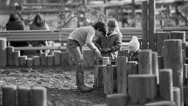 Spielende Kinder auf einem öffentlichen Spielplatz.