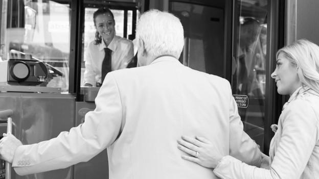 Eine Frau hilft einem älteren Mann.