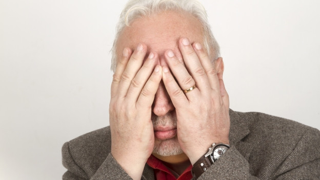 Ein Mann hält sich die Hände vor das Gesicht.