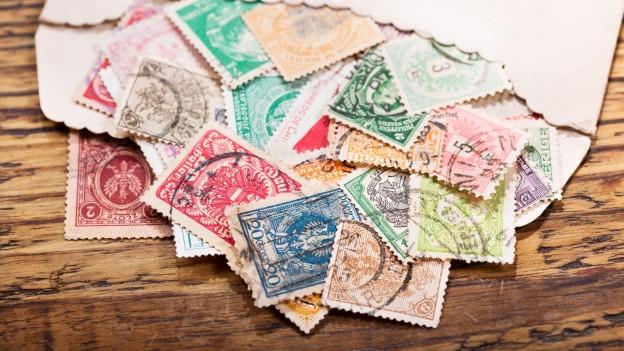 Briefmarken liegen in einem Couvert.