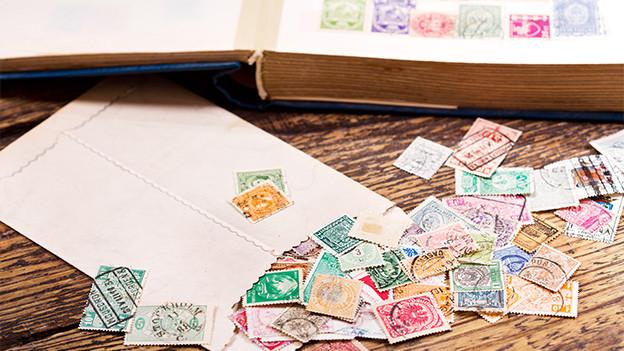 Ein Couvert, Briefmarken und ein Sammelbuch.