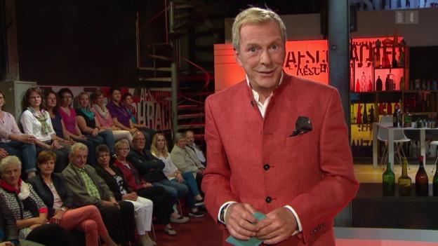 Moderator in rotem Blazer während TV-Sendung.