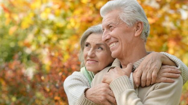 Seniorenpaar umarmt sich vor herbstlich gefärbtem Baum.