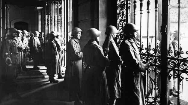 Soldaten bewachen das Bundeshaus und blicken durch die Fenster ins Freie.