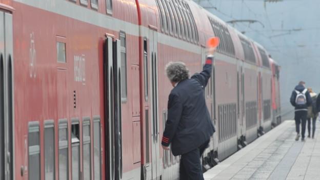 Schaffner gibt Zug Zeichen zum weiterfahren.