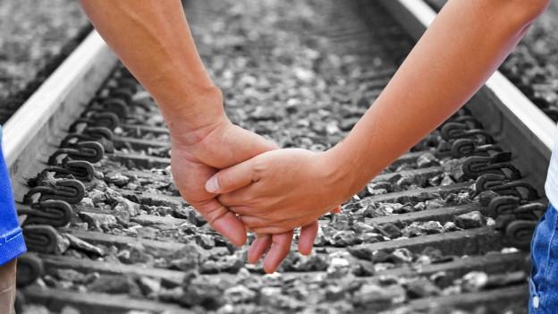Paar gibt sich die Hand vor Geleise.