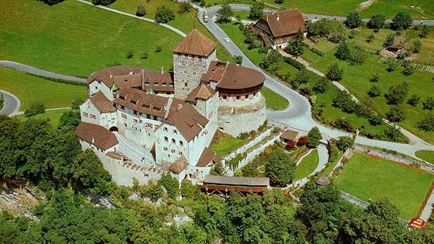 Ein stattliches Schloss auf einem Hügel.