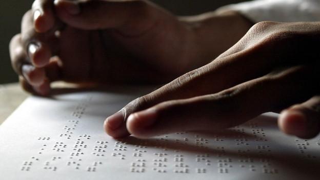 Eine blinde Person liest Blindenschrift mit den Zeigefingern.