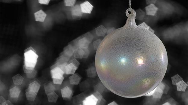 Eine Weihnachtskugel aus Glas an einem Tannenzweig.