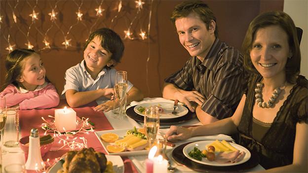 Eine vierköpfige Familie sitzt an einem reich gedeckten Tisch.