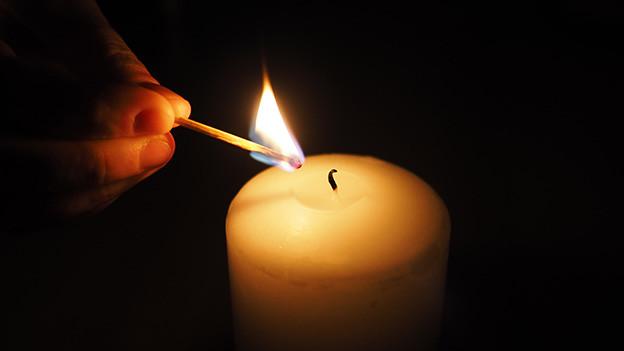 Streichholz und Kerze.