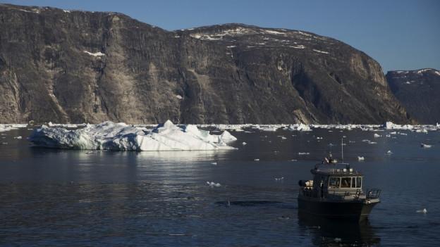 Ein Schiff auf dem Meer mit einem Eisberg in Grönland.