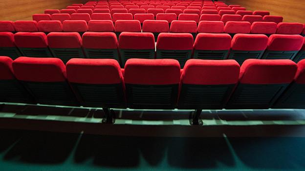 Mehrere Reihen leere Sessel in einem Theater.