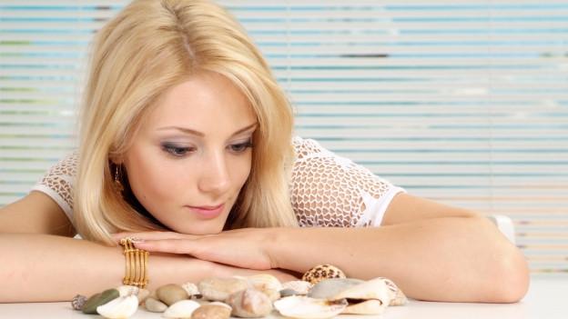 Eine zarte, junge Frau schaut auf ihre Muschelsammlung.