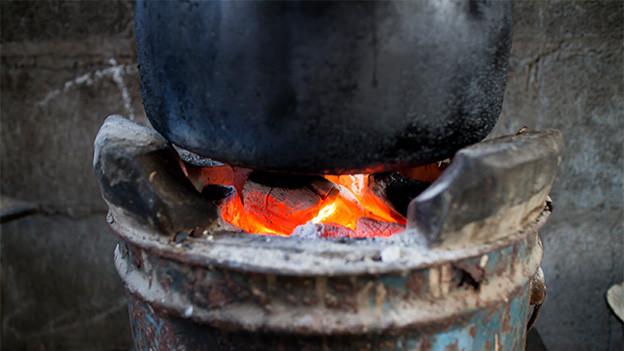 Ein alter schwarzer Kopftopf auf offenem Feuer.