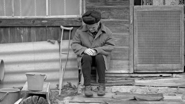 Alter kranker Mann sitzt vor einem Siechenhaus.