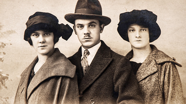 Altes Foto mit einem Gruppenbild von einem Mann zwischen zwei Frauen.