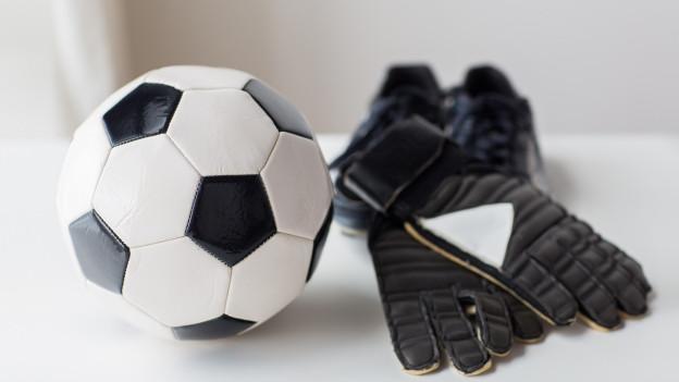 Ein Fussball und ein paar Goalie-Handschuhe.