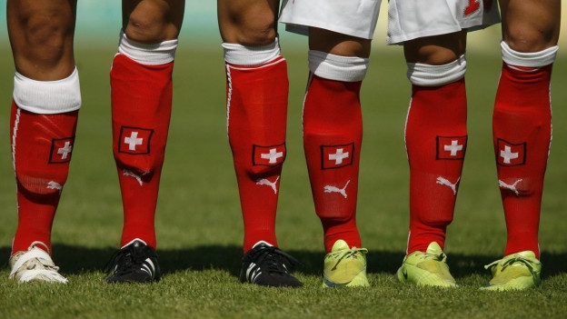 Rote Fussballstulpen mit Schweizerkreuz darauf.