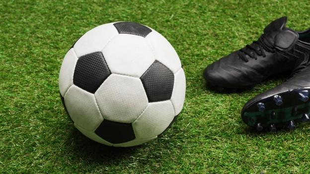 Fussballschuhe und ein Fussball auf einer Wiese.