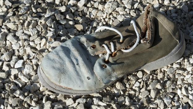 Kaputter Schuh liegt auf dem Kies.