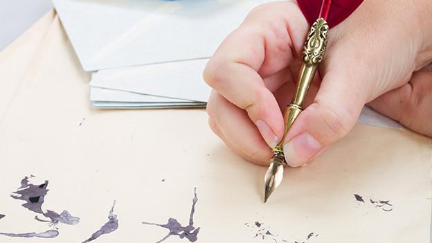 Eine Hand hält eine Füllfeder und schreibt damit auf ein Papier mit Tintenflecken.